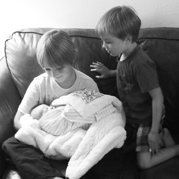 Big Guy and Little Man holding their new cousin.