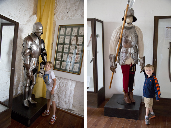 The boys posing with suits of armor.