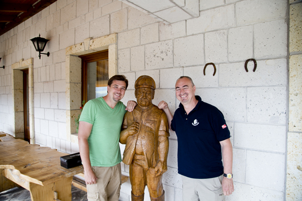 David and Péter posing with a wood statue of the owner.